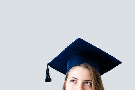 Photo of female university student at graduation with her education being paid for through mortgage refinancing
