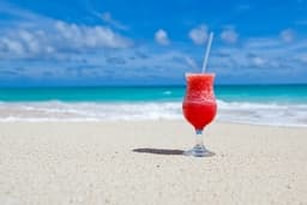 Picture of a cold tropical drink on a beach by the ocean representing a vacation which can be purchased by refinancing a mortgage