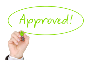 Picture of a hand writing the word approved representing getting approved for a mortgage or home loan