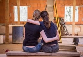 Picture of two girls sitting down happy about their renovation project that they funded from mortgage refinancing