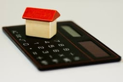 Picture of a mortgage calculator with a toy house on top of it representing the calculation of a mortgage refinance contract