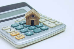 toy house perched on top of a calculator representing a mortgage preapproval calculation